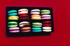 Tasty different colored macarons in black box on red backgroundn stock image