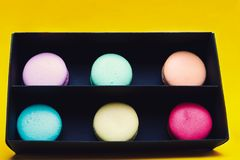 Tasty different colored macarons in black box royalty free stock photography