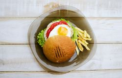 Tasty dinner with fast food. Burger with eggs, tomato, salad and. French fries with sauces on the glass plate. White wooden table with food Royalty Free Stock Photos