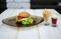 Tasty dinner with fast food. Burger with eggs, tomato, salad and. French fries with sauces on the glass plate. White wooden table with food Royalty Free Stock Photo