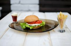 Tasty dinner with fast food. Burger with eggs, tomato, salad and. French fries with sauces on the glass plate. White wooden table with food Stock Photo