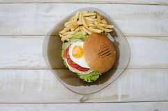 Tasty dinner with fast food. Burger with eggs, tomato, salad and. French fries on the glass plate. White wooden table with food Royalty Free Stock Images
