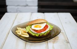 Tasty dinner with fast food. Burger with eggs, tomato, salad and. French fries with sauces on the glass plate. White wooden table with food Royalty Free Stock Images