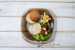 Tasty dinner with fast food. Burger with eggs, tomato, salad and. French fries with sauces on the glass plate. White wooden table with food Stock Photos