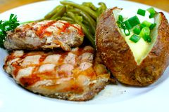 A tasty dinner with green bean. Delicious pork chop meal with a baked potato Stock Image