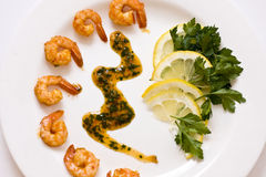 Tasty dish consist of shrimps. Sauce, lemon and greens on a white plate royalty free stock images