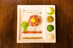 Tasty dish of raw meat, egg yolk, greens and spices placed on the white rectangular plate. The above view. Stock Photo