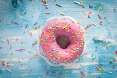 Tasty donut with pink icing and colorful sprinkles. On blue wooden background royalty free stock photo