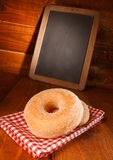 Tasty donut with vanilla sugar and a menu board Royalty Free Stock Photos