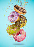 Tasty doughnuts in motion falling on pastel blue background. Stock Photo