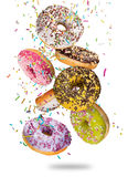 Tasty doughnuts in motion falling on white background. Tasty doughnuts in motion falling on white background, close-up Stock Images