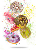 Tasty doughnuts in motion falling on white background. Tasty doughnuts in motion falling on white background, close-up Royalty Free Stock Photo