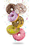 Tasty doughnuts in motion falling on white background. Royalty Free Stock Photo