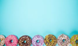 Tasty doughnuts on pastel blue background. Royalty Free Stock Image