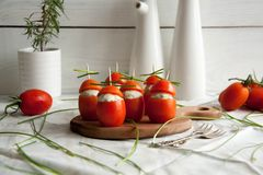Stuffed tomato with chicken, garlic and cream cheese pasta lying on a brown wooden board. Tasty and easy breakfast idea: Stuffed tomato with chicken, garlic and stock photography