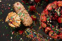 Tasty eclairs and fresh summer berry cake. With fruits on tray, closeup, top view Royalty Free Stock Photography