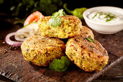 Tasty falafel patties with chickpea and fava beans. Tasty Turkish falafel patties with chickpea and fava beans served on an old rustic wooden board with salad Royalty Free Stock Image