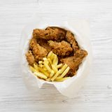 Tasty fast food: fried chicken drumsticks, spicy wings, French fries and chicken strips in a paper box over white wooden. Background, top view. Flat lay stock images