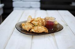 Tasty fast food fried pies on the glass plate on the white woode Royalty Free Stock Image