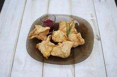 Tasty fast food fried pies on the glass plate on the white woode Stock Photography