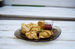 Tasty fast food fried pies on the glass plate on the white woode Royalty Free Stock Photography
