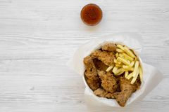 Tasty fastfood: fried chicken drumsticks, spicy wings, French fries and chicken strips in paper box, sauce on a white wooden backg. Round, overhead view. Flat stock photography