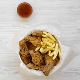 Tasty fastfood: fried chicken drumsticks, spicy wings, French fries and chicken strips in paper box, sauce on a white wooden. Surface, top view. Flat lay stock photography