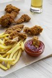 Tasty fastfood: fried chicken drumsticks, spicy wings, French fries and chicken strips with sour-sweet sauce and cold beer over wh. Ite wooden background, low royalty free stock photography