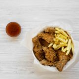 Tasty fastfood: fried chicken drumsticks, spicy wings, French fries and chicken strips in paper box, sour-sweet sauce on a white. Wooden table, top view. Flat royalty free stock images
