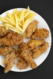 Tasty fastfood: fried chicken drumsticks, spicy wings, French fries, chicken strips on white plate over black surface, top view. Flat lay, overhead royalty free stock image