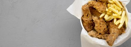Tasty fastfood: fried chicken legs, spicy wings, French fries and chicken strips in paper box over gray surface, top view. Space. Tasty fastfood: fried chicken stock images