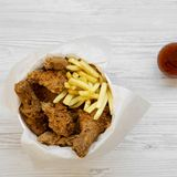 Tasty fastfood: fried chicken legs, spicy wings, French fries, chicken strips in paper box, sauce over white wooden background,. Top view. Flat lay, overhead royalty free stock photos