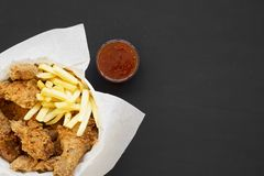 Tasty fastfood: fried chicken legs, spicy wings, French fries and chicken strips in paper box, sour-sweet sauce on black. Background, top view. Flat lay stock image