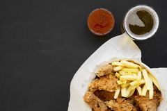 Tasty fastfood: fried chicken legs, spicy wings, French fries and chicken strips in paper box, sour-sweet sauce, cold beer on. Black surface, top view. Flat lay royalty free stock photo