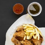 Tasty fastfood: fried chicken legs, spicy wings, French fries and chicken strips in paper box, sour-sweet sauce, cold beer on. Black table, top view. Flat lay royalty free stock image