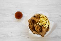 Tasty fastfood: fried chicken legs, spicy wings, French fries and chicken strips in paper box, sour-sweet sauce on a white wooden. Background, top view. Flat stock images