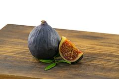 Tasty figs on wooden board. Photo of figs with slice and leaves on wooden board. Autumn season food photo. royalty free stock photography