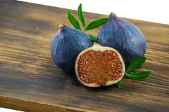 Tasty figs on wooden board. Photo of figs with slice and leaves on wooden board. Autumn season food photo. stock photo