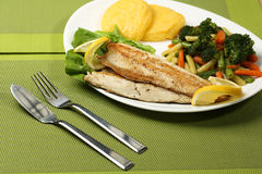 Tasty fish with lemon and vegetables Royalty Free Stock Images
