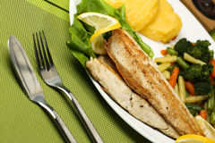 Tasty fish with lemon and vegetables Royalty Free Stock Photo