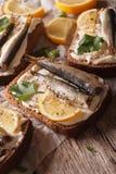 Tasty fish sandwiches with sprats, cream cheese and lemon macro Stock Photo