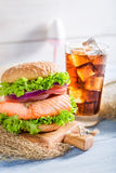 Tasty fishburger with salmon served with cold drink Royalty Free Stock Photos