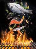 Tasty fishes flying above cast iron grate with fire flames. Freeze motion barbecue concept stock photography
