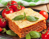 Tasty flavorful lasagna on a plate and ingredients.  Royalty Free Stock Photography