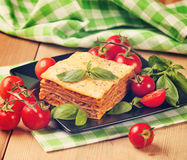 Tasty flavorful lasagna on a plate and ingredients. Vintage retr Royalty Free Stock Photography
