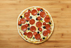 Tasty, flavorful pizza on wooden background. Stock Photos