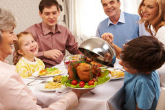 Tasty food. Portrait of happy family sitting at festive table and holding each other by hands Stock Photos