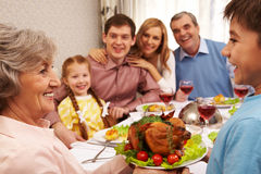Tasty food. Portrait of happy grandmother holding tray with roasted turkey and looking at her grandson