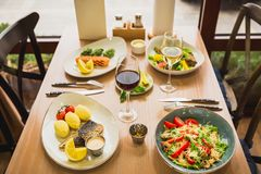 Tasty food with fish dishes and glass of wine in restaurant stock photos