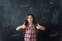 Hungry girl feeling happy after eating her favorite food. Tasty food. Little cute girl feeling good and putting her thumbs up after having a delicious meal stock photos